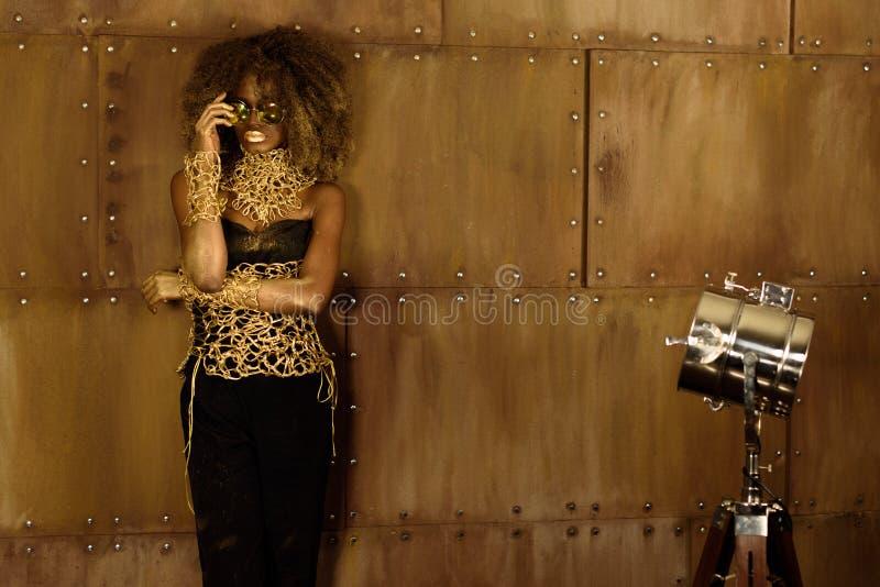 Ritratto dello studio di una donna afroamericana con trucco dorato e degli occhiali da sole che posano tenersi per mano vicino al fotografia stock