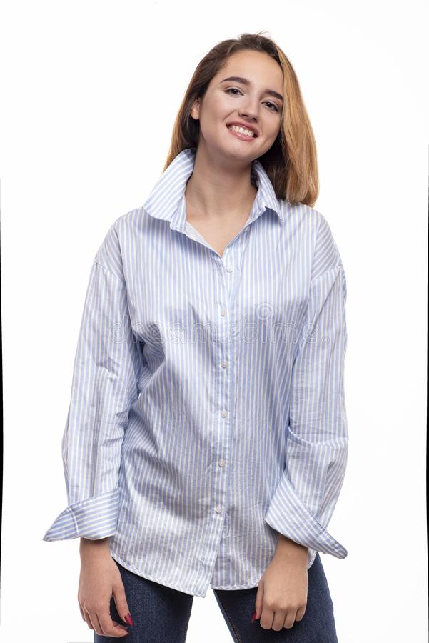Ritratto dello studio di una donna sorridente con i jeans d'uso e la blusa dei capelli biondi lunghi, isolato su whait fotografia stock libera da diritti