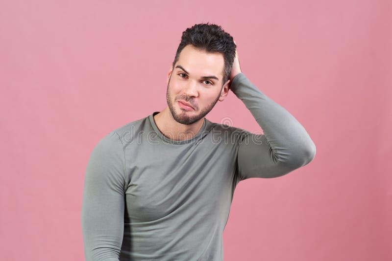 Ritratto dello studio su un fondo isolato di giovane uomo atletico che sorride e che graffia la sua testa che pondera la proposta immagine stock