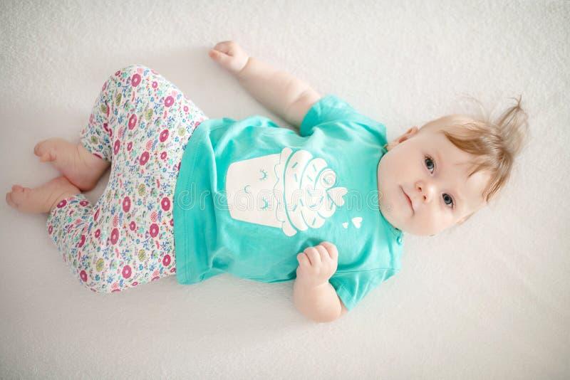 Ritratto di adorabile bimba con occhi blu e capelli carini che guarda la telecamera tranquillamente con curiosità fotografie stock