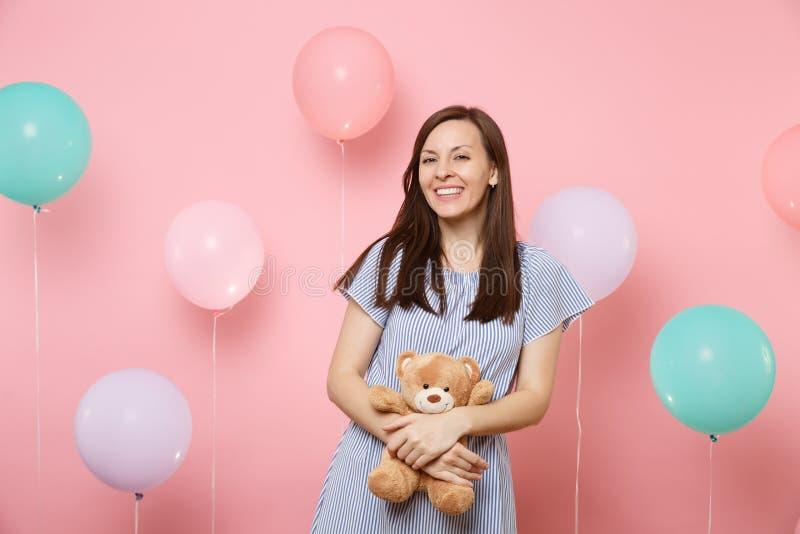 Ritratto di affascinare giovane donna allegra in vestito blu che tiene e che abbraccia il giocattolo della peluche dell'orsacchio fotografie stock