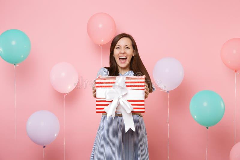 Ritratto di affascinare giovane donna felice in vestito blu che tiene scatola rossa con il presente del regalo su fondo rosa past immagine stock