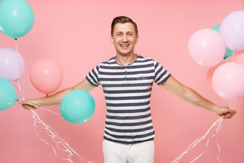 Ritratto di affascinare la maglietta a strisce d'uso del giovane uomo felice che giudica gli aerostati variopinti isolati su lumi fotografia stock