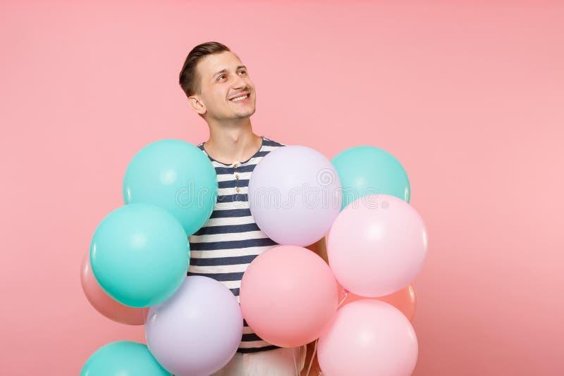 Ritratto di affascinare la maglietta a strisce d'uso del giovane uomo felice che giudica gli aerostati variopinti isolati su lumi fotografia stock libera da diritti