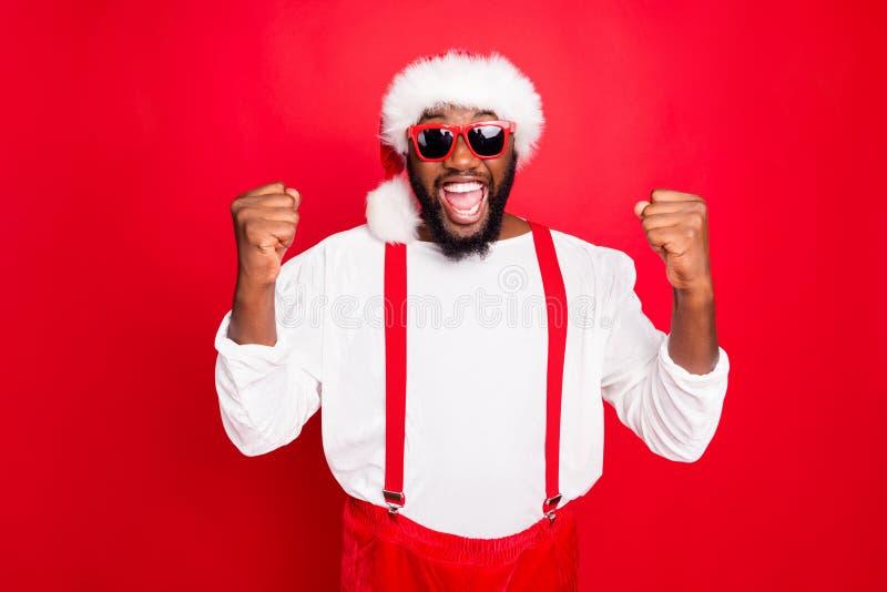 Ritratto di allegro Babbo Natale africano a xmas che urlano sì alzando i pugni hanno una festa di massa con un pullover bianco immagine stock libera da diritti