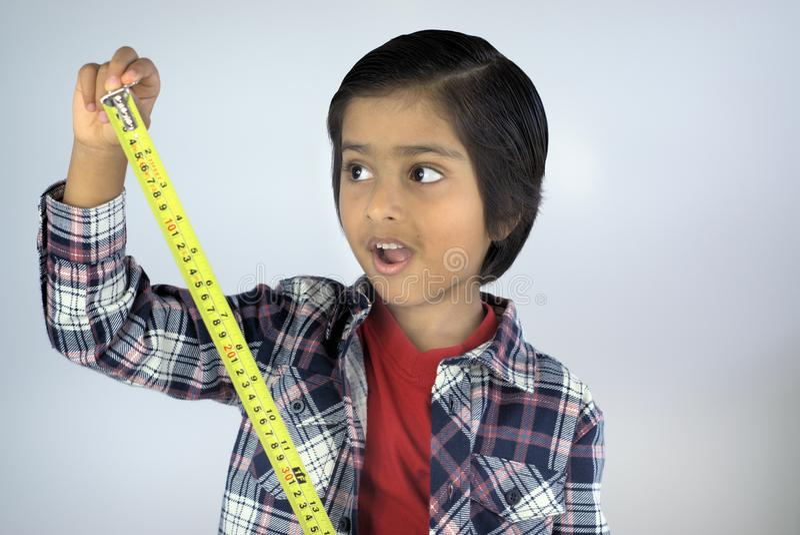 Ritratto di altezza di misurazione del ragazzino immagini stock
