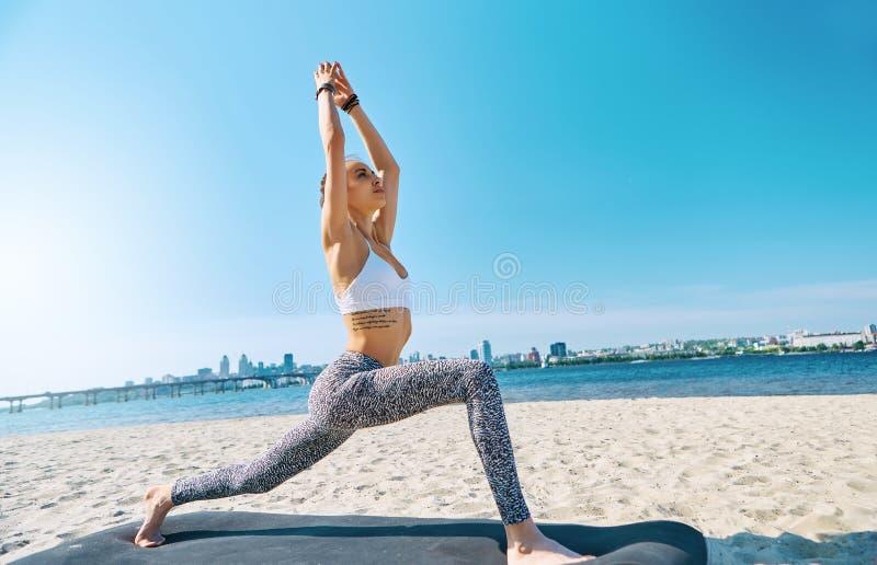 Ritratto di aria aperta di giovane condizione atletica esile della donna nel asana di yoga con le mani sollevate sulla città e su fotografia stock libera da diritti
