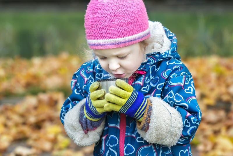 Ritratto di autunno del primo piano della bambina che beve bevanda calda dalla tazza inossidabile della boccetta del termos fotografie stock