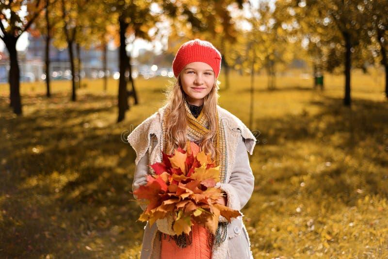Ritratto di autunno della ragazza sveglia in cappello e cappotto rossi immagini stock libere da diritti