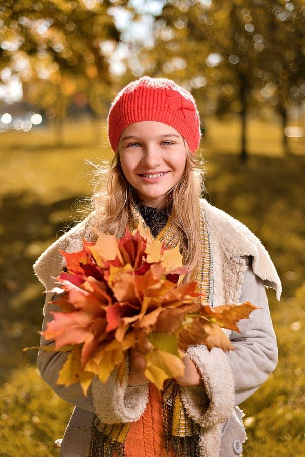 Ritratto di autunno della ragazza sveglia in cappello e cappotto rossi immagine stock