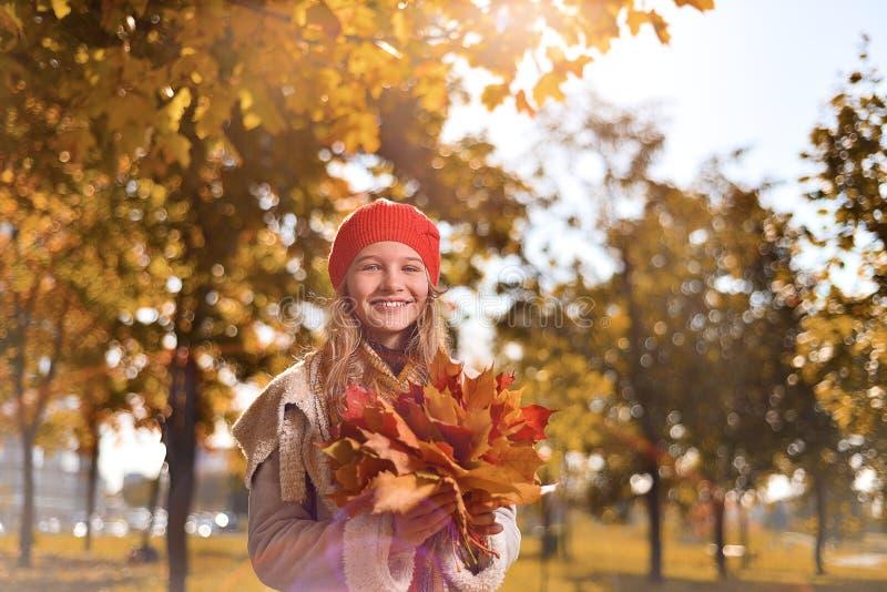 Ritratto di autunno della ragazza sveglia in cappello e cappotto rossi fotografia stock