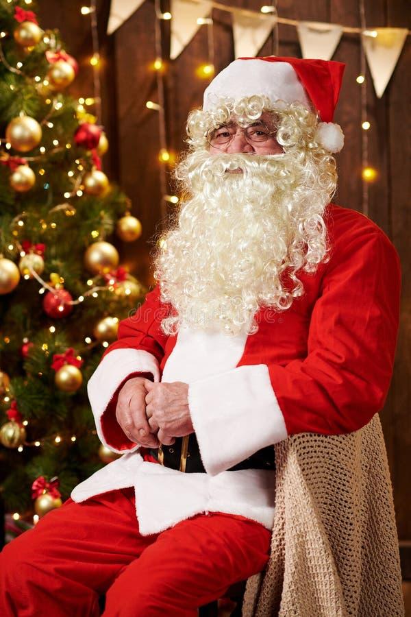 Ritratto di Babbo Natale, seduto al chiuso vicino a un albero decorato di Natale con delle luci - Buon Natale e buone vacanze fotografia stock libera da diritti