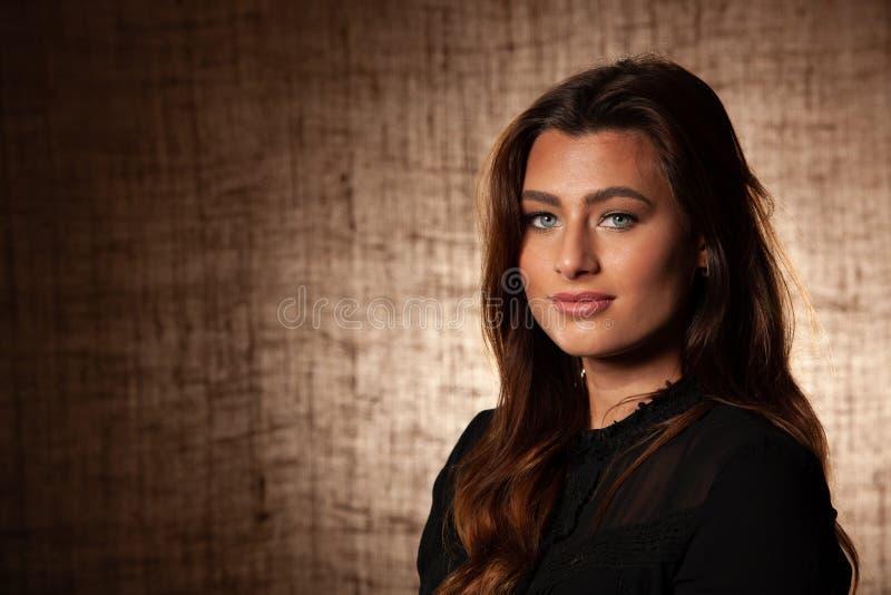Ritratto di BBeauty della donna castana sveglia con gli occhi azzurri sopra il fondo di marrone di lerciume fotografie stock