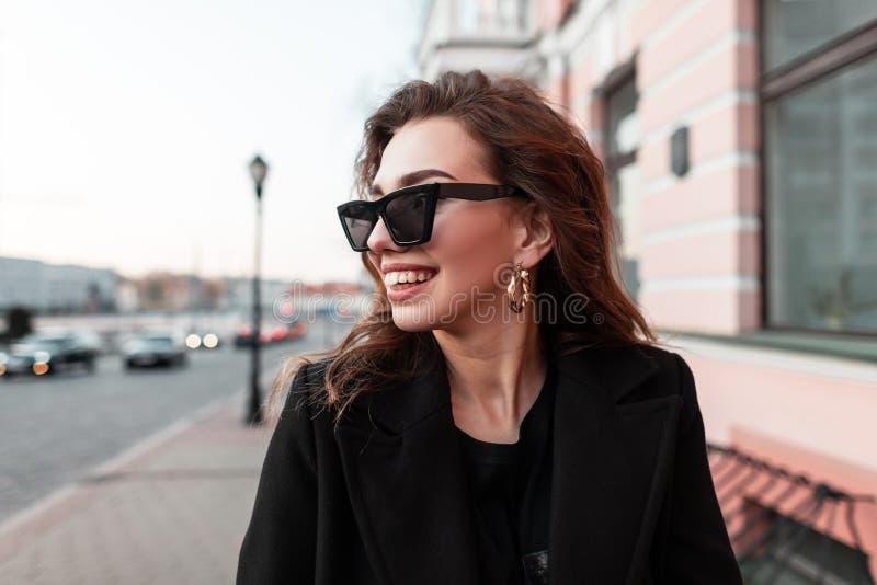 Ritratto di bei pantaloni a vita bassa allegri della giovane donna in occhiali da sole alla moda con un sorriso in un cappotto al fotografia stock
