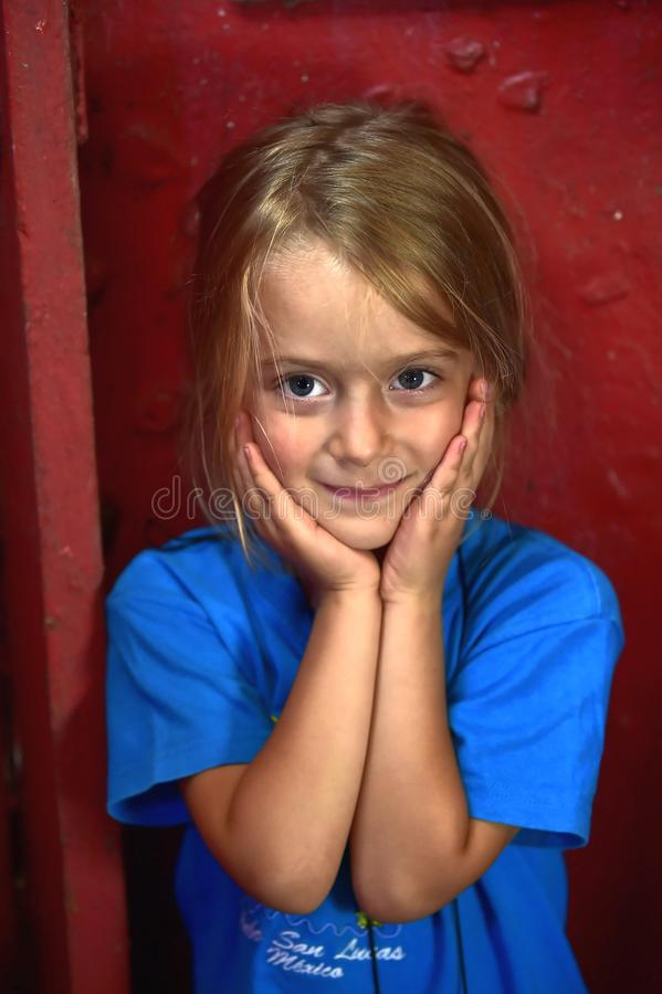 Ritratto di bella bambina sul fondo rosso della parete fotografia stock libera da diritti