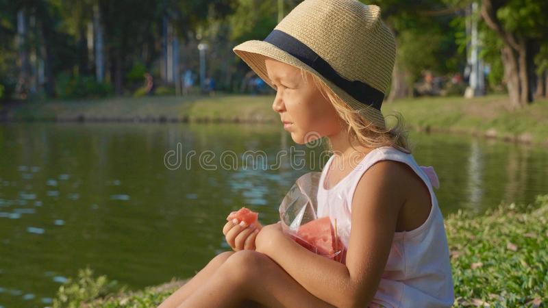 Ritratto di bella bambina sveglia che mangia anguria con piacere fotografia stock