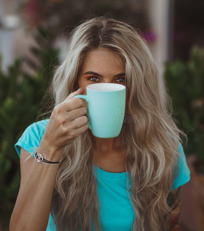 Ritratto di bella bionda con gli occhi espressivi Tenuta della tazza di caffè Il concetto di colore del turchese moderno fotografia stock