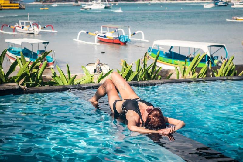 Ritratto di bella donna abbronzata in swimwear nero che si rilassa nella stazione termale della piscina Giorno di estate caldo e  fotografia stock