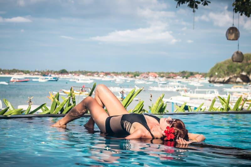 Ritratto di bella donna abbronzata in swimwear nero che si rilassa nella stazione termale della piscina Giorno di estate caldo e  fotografie stock