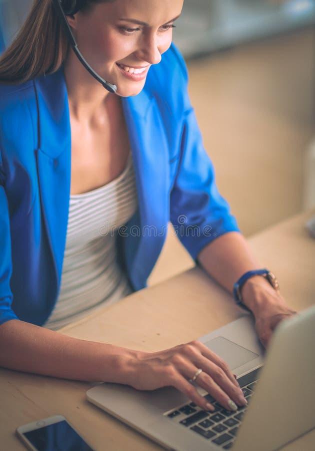 Ritratto di bella donna di affari che lavora al suo scrittorio con la cuffia avricolare ed il computer portatile immagine stock
