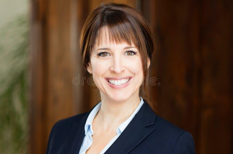 Ritratto di bella donna di affari che sorride alla macchina fotografica fotografia stock