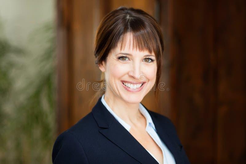 Ritratto di bella donna di affari che sorride alla macchina fotografica immagine stock