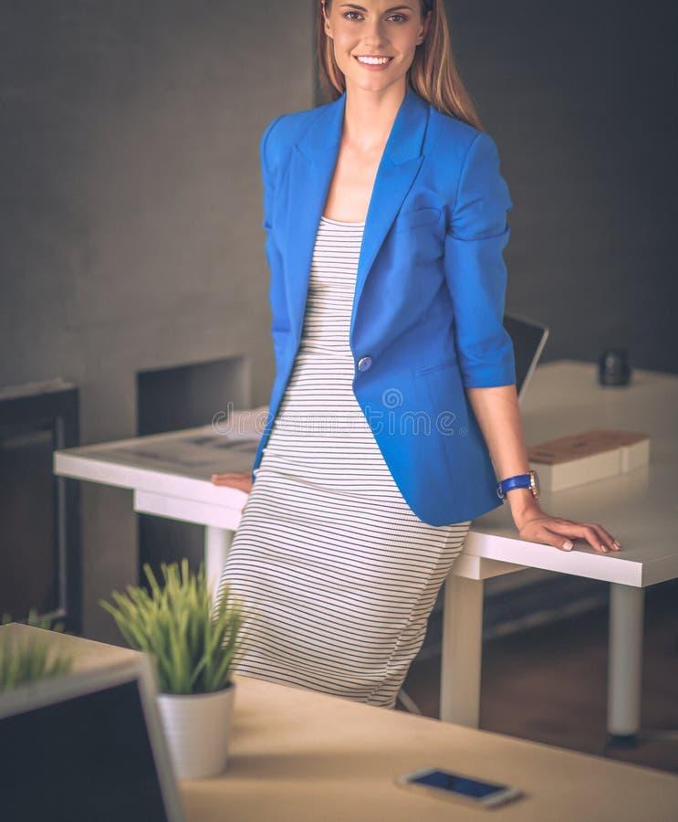 Ritratto di bella donna di affari che sta vicino al suo posto di lavoro immagini stock libere da diritti