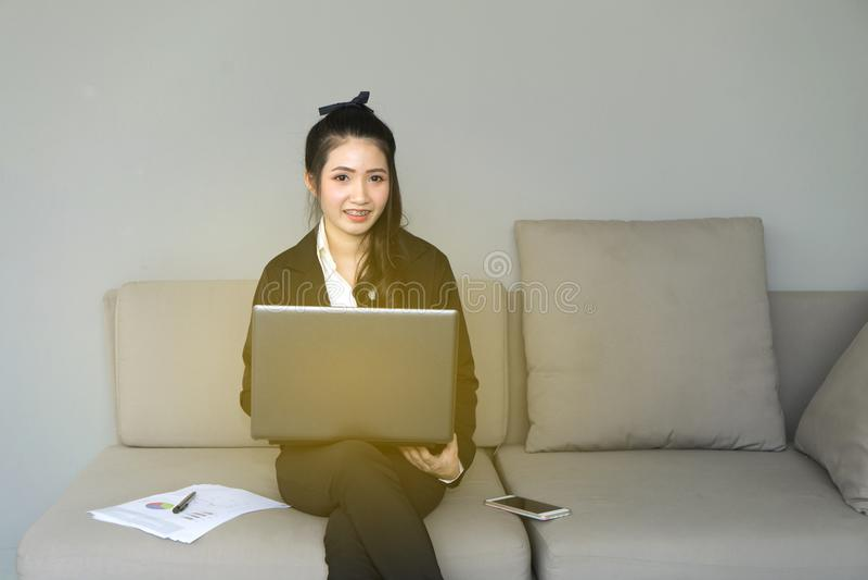 Ritratto di bella donna di affari sul vestito nero facendo uso di un lapto fotografie stock