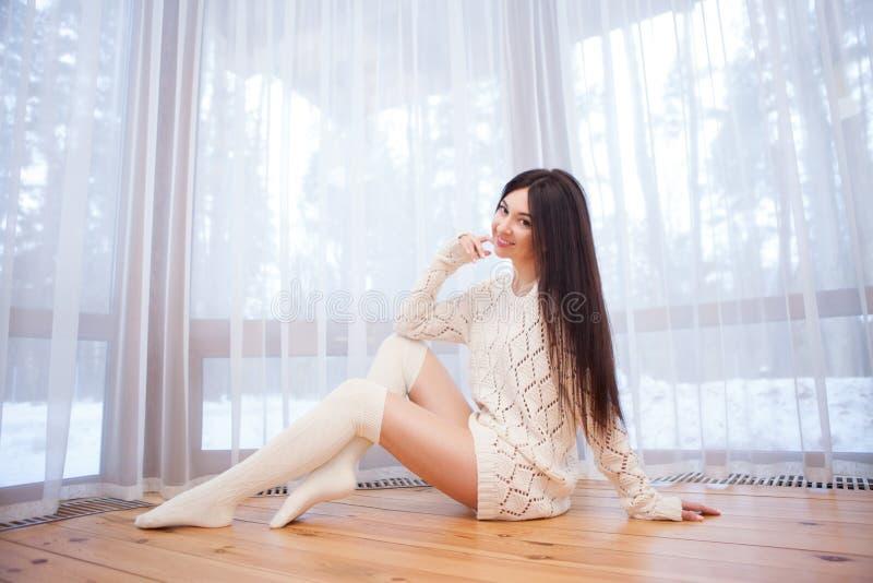 Ritratto di bella donna alla moda felice che si siede sul pavimento vicino alla finestra alla casa Foresta di inverno alla finest immagine stock