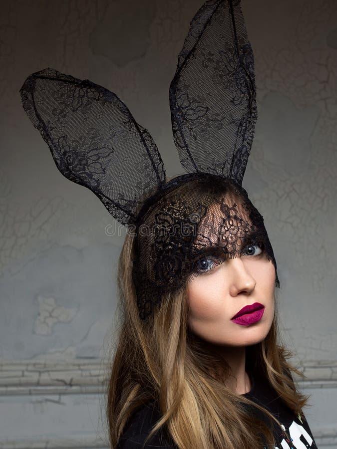 Ritratto di bella donna alla moda in orecchie del pizzo del coniglietto fotografie stock