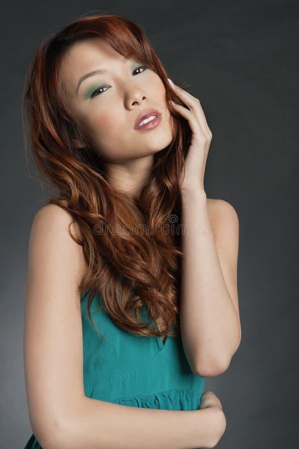 Ritratto di bella donna asiatica che posa sopra il fondo colorato fotografia stock libera da diritti