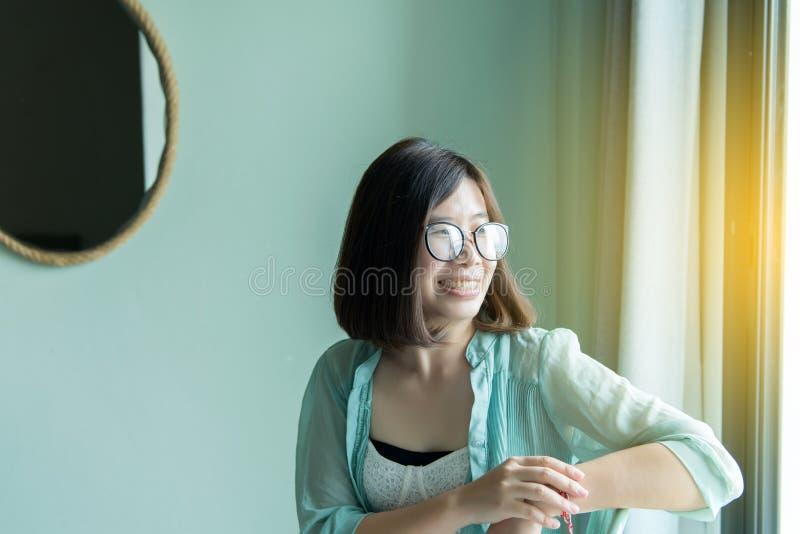 Ritratto di bella donna asiatica rilassarsi e sedendosi vicino alla finestra a casa, pensiero positivo, atteggiamento buon fotografia stock libera da diritti