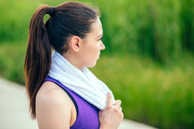 Ritratto di bella donna attraente sportiva che corre nel parco sul fondo della natura Giorno soleggiato, allenamento duro sport fotografia stock