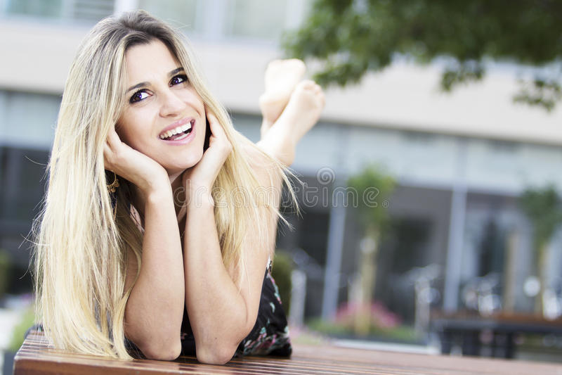 Ritratto di bella donna bionda che si trova su un banco immagine stock