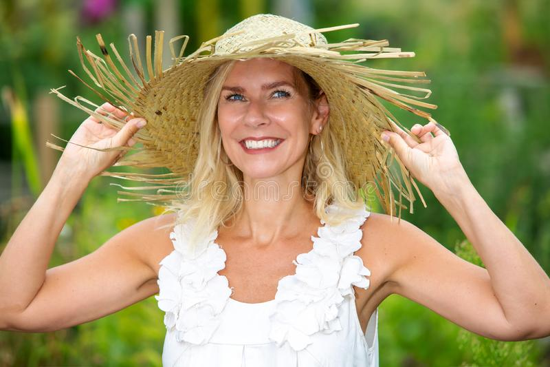 Ritratto di bella donna bionda con la condizione del cappello di paglia fuori fotografia stock libera da diritti