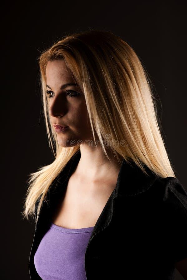 Ritratto di bella donna bionda sopra fondo grigio scuro immagini stock