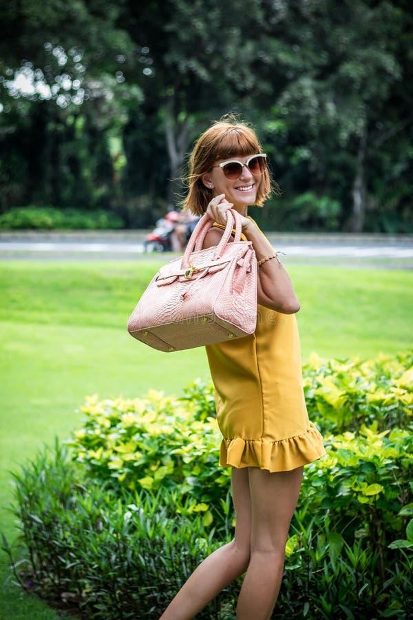 Ritratto di bella donna castana caucasica alla moda con gli occhiali da sole e la posa di lusso della borsa del pitone dello snak immagine stock