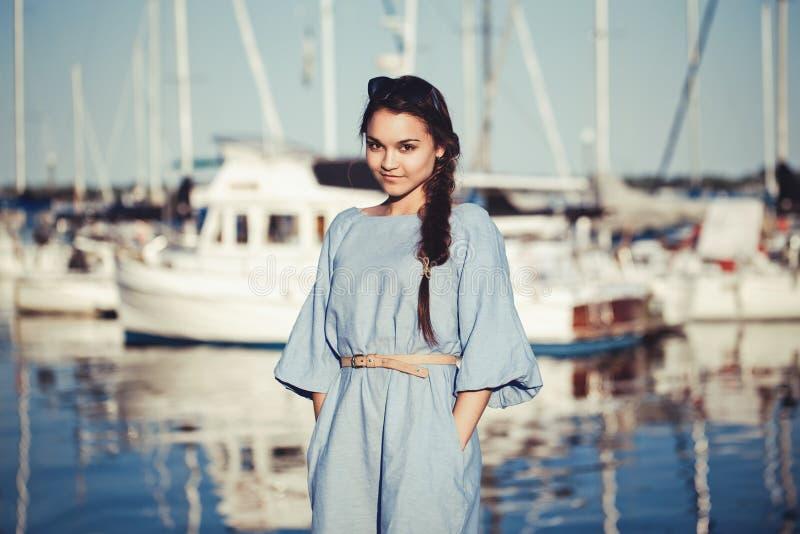 Ritratto di bella donna castana caucasica bianca con pelle abbronzata in vestito blu, dalla spiaggia lakeshore fotografia stock