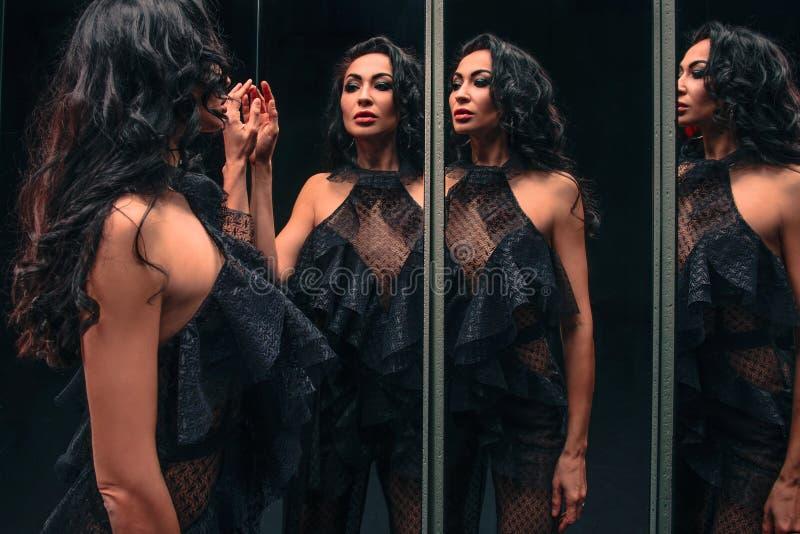 Ritratto di bella donna castana che sta vicino agli specchi immagine stock