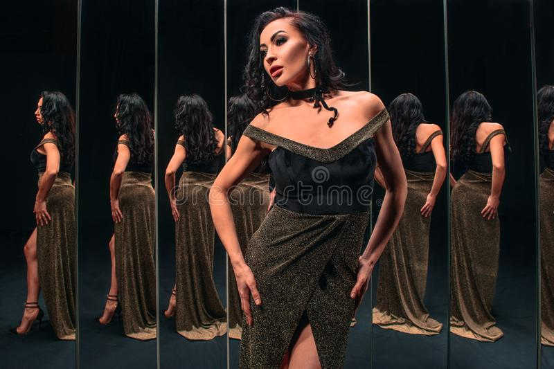 Ritratto di bella donna castana che sta vicino agli specchi fotografia stock