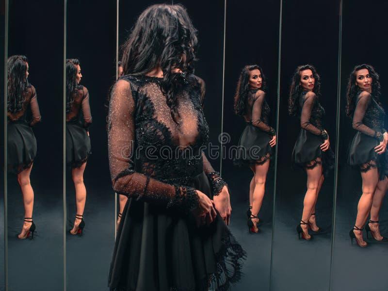 Ritratto di bella donna castana che sta vicino agli specchi immagini stock