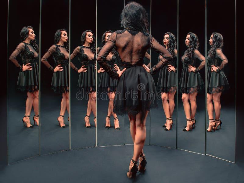 Ritratto di bella donna castana che sta vicino agli specchi fotografie stock