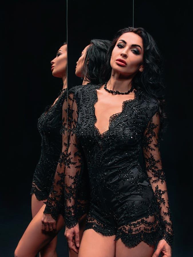 Ritratto di bella donna castana che sta vicino agli specchi fotografie stock libere da diritti