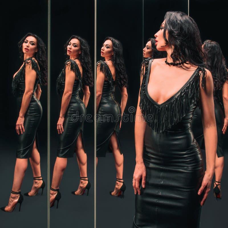 Ritratto di bella donna castana che sta vicino agli specchi fotografia stock libera da diritti