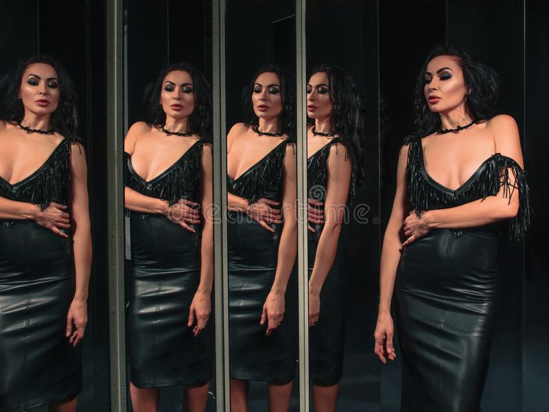 Ritratto di bella donna castana che sta vicino agli specchi immagini stock libere da diritti