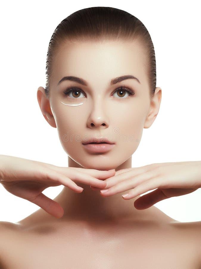 Ritratto di bella donna che applica una certa crema al suo fronte per cura di pelle fotografie stock