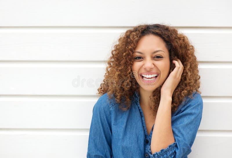 Ritratto di bella donna che ride con la mano in capelli fotografia stock