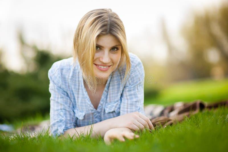 Ritratto di bella donna che risiede nell'erba con un sorriso fotografie stock