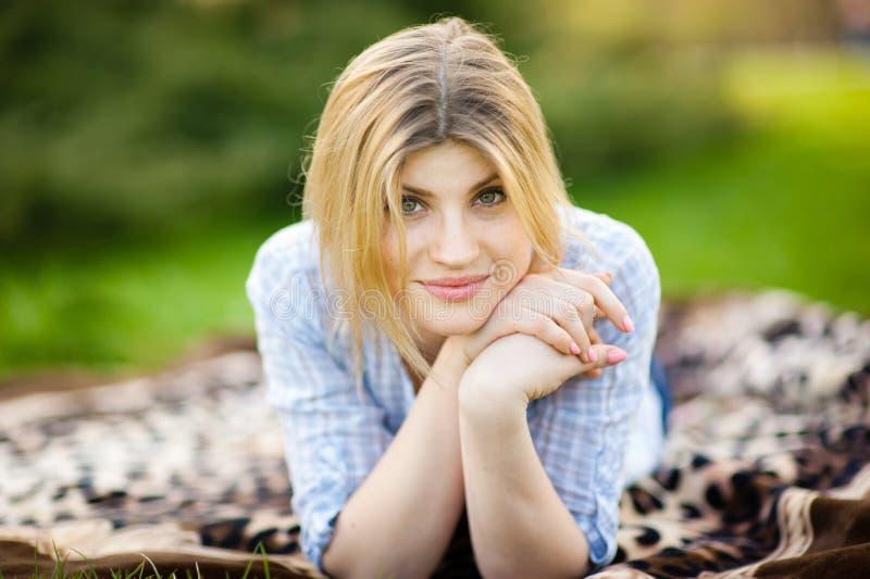 Ritratto di bella donna che risiede nell'erba con un sorriso fotografia stock