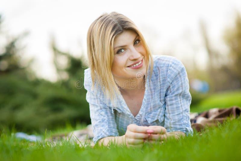 Ritratto di bella donna che risiede nell'erba con un sorriso fotografie stock libere da diritti